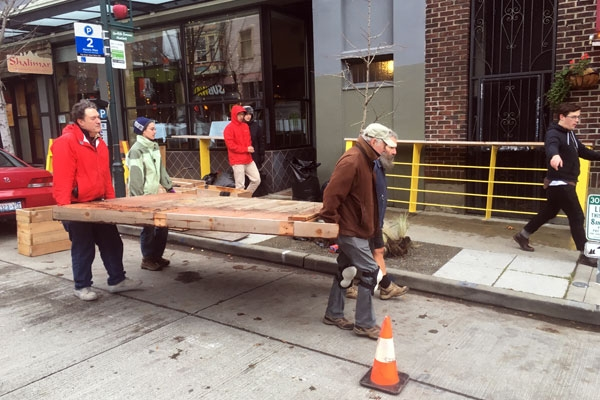 Carrying the parklet in pieces down the street to its new location